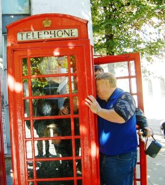 Team climbing into a phone box as a treasure hunt challenge.