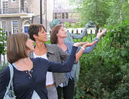 Three women doing a pose as a tree.