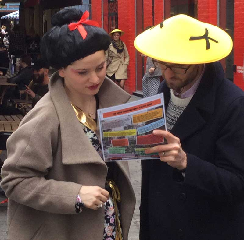Two people read a riddle on their Chinatown treasure hunt.