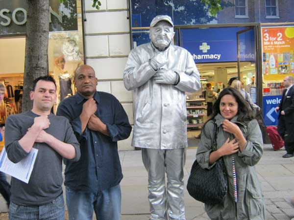 Three people posing with a human statue in Covent Garden.
