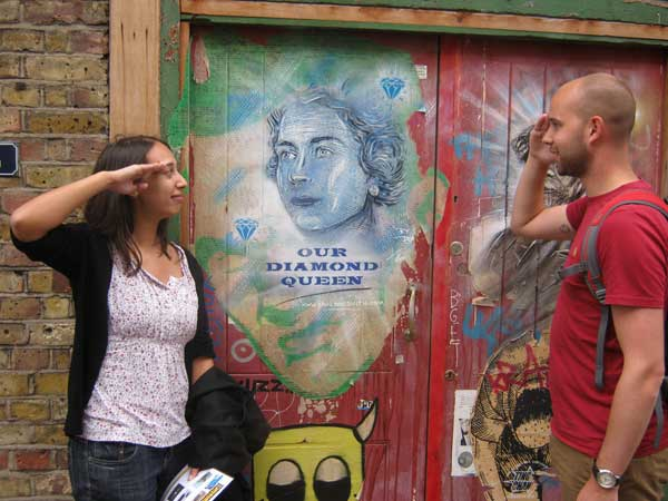Team members saluting a portrait of the Queen on a Spitalfields wall.