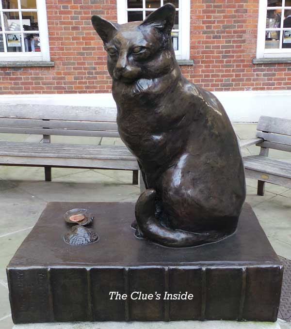 A statuette of Hodge the cat sitting on top of a copy of Dr Johnson's dictionary.