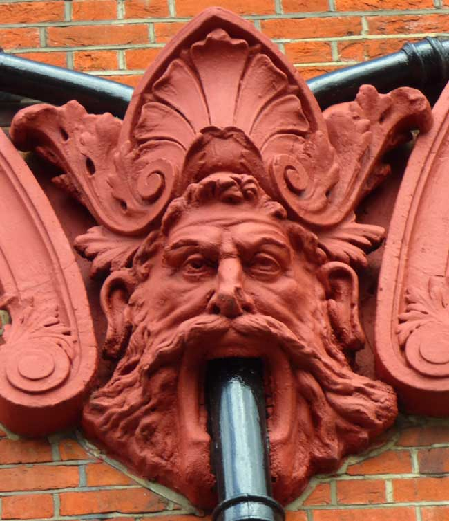 A carved face with a drainpipe coming out of its mouth.