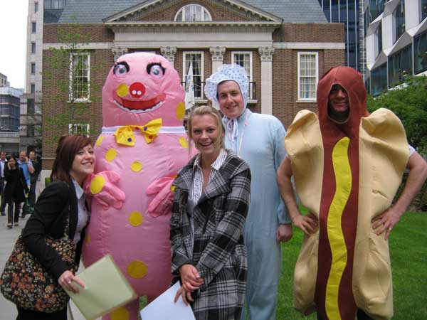 Two participants posing with a man in a Mr. Blobby suit as part of a City challenge.
