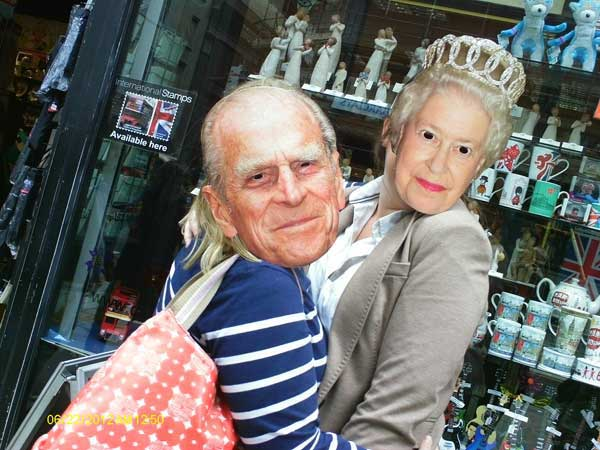 Two treasure hunt participants wearing masks of the Queen and Prince Phillip.