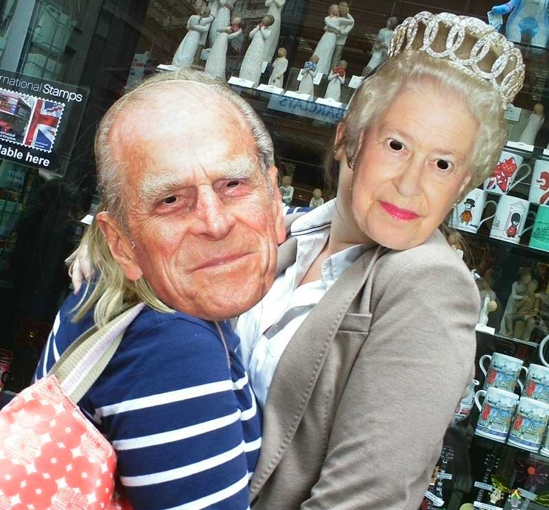 Two team members wearing masks of the Queen and Prince Phillip.