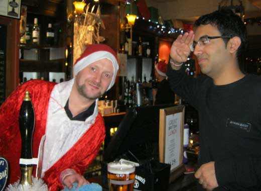 A treasure hunt participant salutes a barman dressed as Santa.