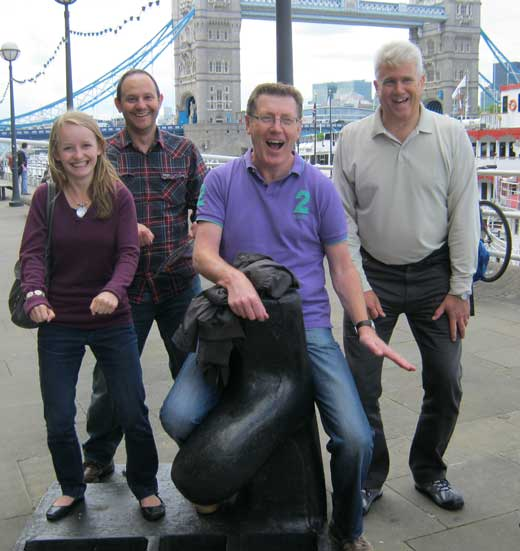 A group on a team building day posing by London's Tower Bridge.