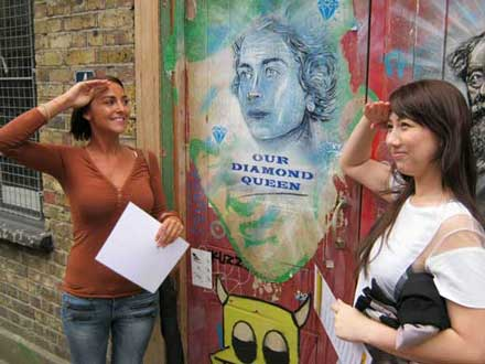 Two girls salute an image of Queen Elizabeth 11 as part of their London team building pose challenge.