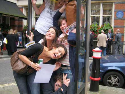 A team crowd into a London phone box.