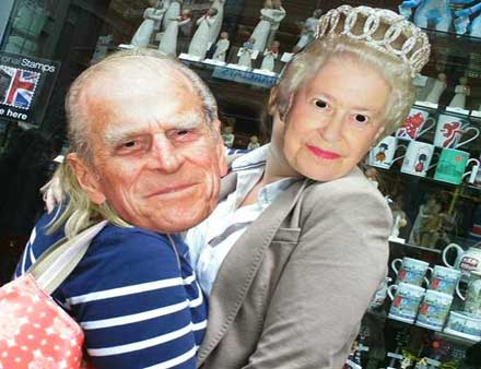 Two members of a team wearing masks of the Queen and Prince Philip.