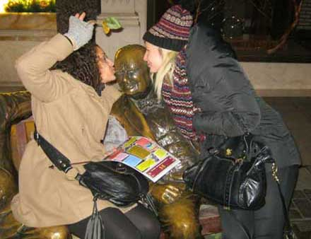 Two ladies kissing Winston Churchill as one of their pose challenges on a team building activity in London.