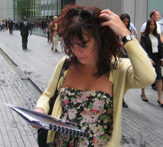 A woman reads a treasure hunt clue and scratches her head.